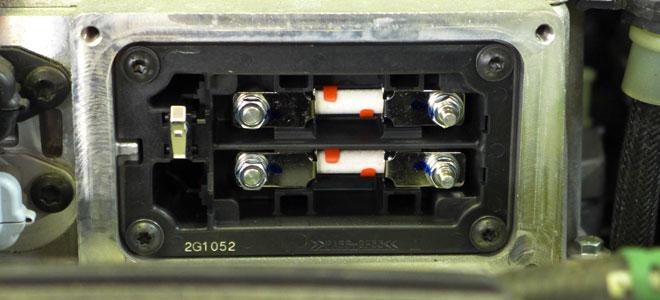 An den Sicherungen in der Hochvoltleitung überprüft der Mechaniker die Spannungsfreiheit.